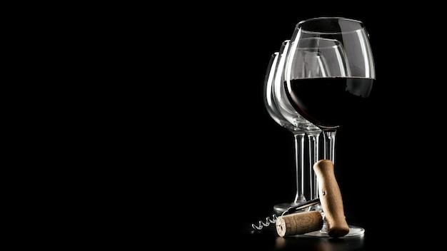 Corkscrew and cork near wineglasses