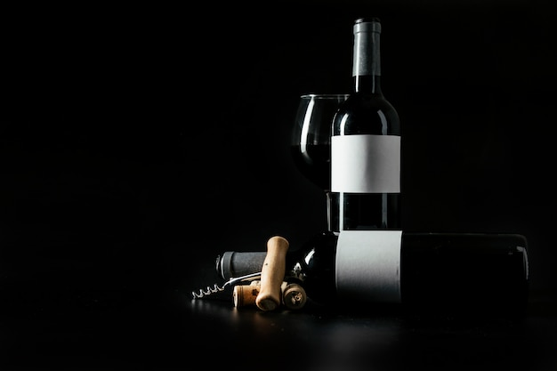 Corkscrew and corks near bottles and wineglass