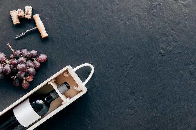 Corkscrew and grape near box with wine