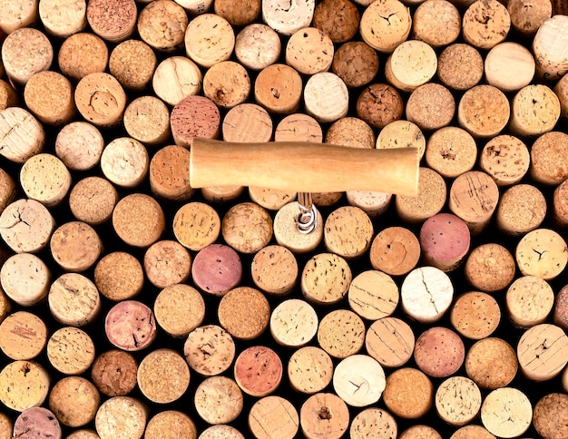 Corkscrew and wine cork background