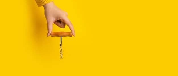 Corkscrew with wooden handle over yellow space