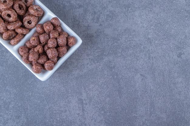 Кукурузные шарики и кукурузные кольца на миске на мраморном фоне.