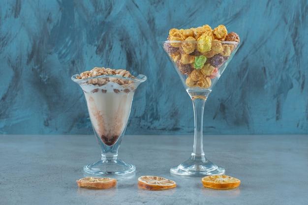 Palline di mais in un bicchiere e fiocchi di mais in un bicchiere da caffè al latte, sul tavolo blu.