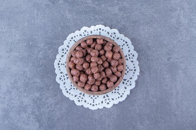 Кукурузные шарики в миске на подставке, на мраморном фоне.