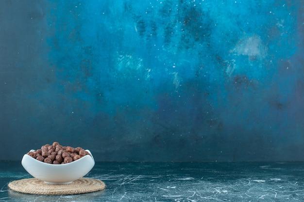Кукурузные шарики в миске на подставке, на синем фоне. фото высокого качества