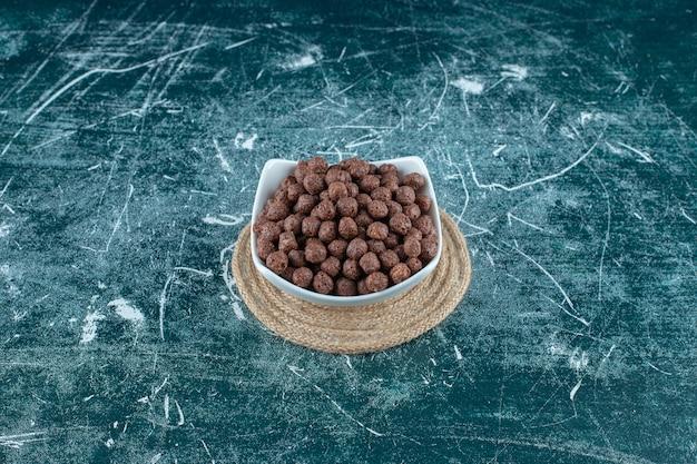 파란색 배경에 trivet에 그릇에 옥수수 공. 고품질 사진