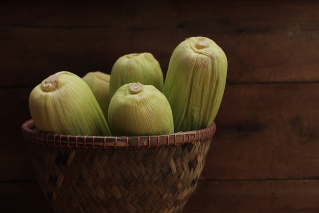 Corn on bamboo rice basket on wooden background