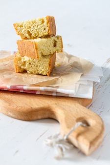 Corn bread cut in peaces on white wood background