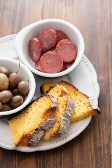 Corn bread with olives and smoked sausages on dish