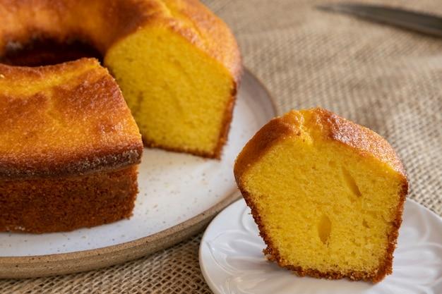 옥수수 케이크와 조각은 하얀 접시와 황마 식탁보에 잘립니다. 선택적 초점