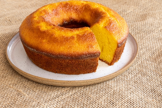 Corn cake with orange on white plate and jute tablecloth.