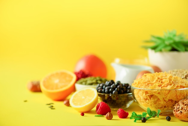 Corn cereal, muesli, milk, berries, orange juice, yogurt, boiled egg, nuts, fruits, banana, peach for breakfast on yellow background.