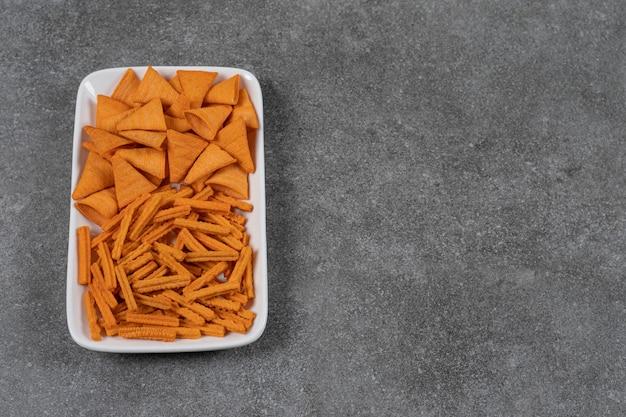 Chip di mais e pane secco in una ciotola sulla superficie di marmo