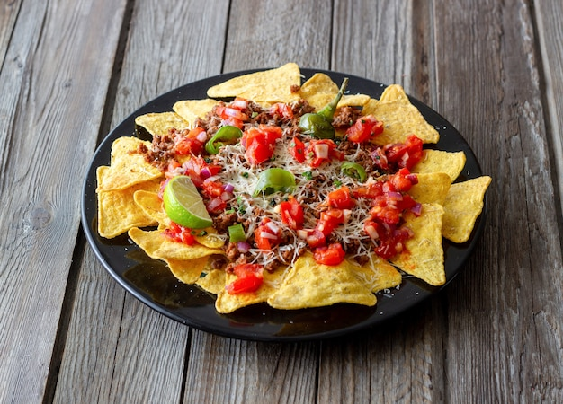 コーンチップスのナチョスに肉、チーズ、トマト、ピーマンを添えます。メキシコ料理。郷土料理。