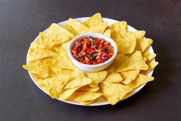 Кукурузные чипсы начос с соусом из сальсы. мексиканская еда. вегетарианская пища.