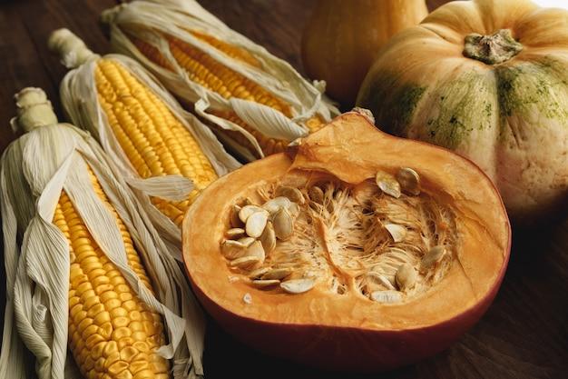 茶色の木板のトウモロコシの穂軸とカボチャをクローズアップ