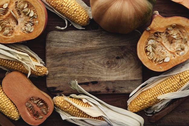 茶色の木の板のトウモロコシの穂軸とカボチャをクローズアップ