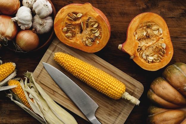 茶色の木の板のトウモロコシの穂軸とカボチャのクローズアップ
