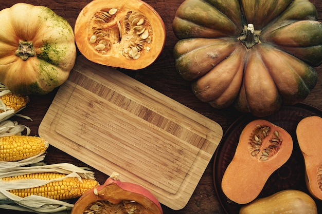 茶色の木の板にトウモロコシの穂軸とカボチャ