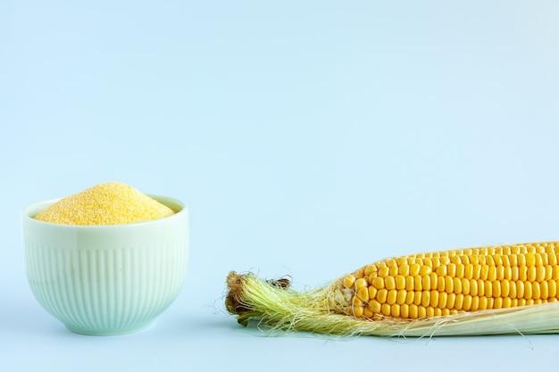 Corn cobs and bowl of corn flour on light blue