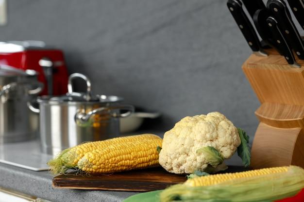 Corn cobs and cauliflower on kitchen counter