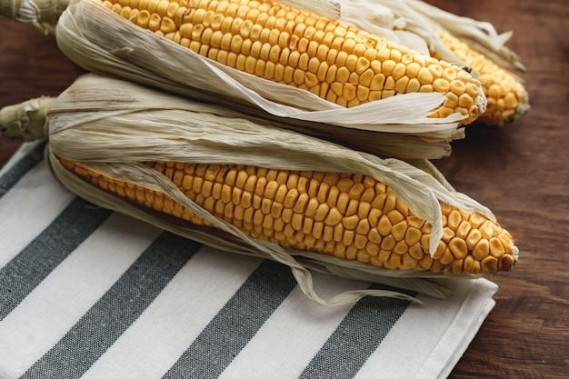 Corn cobs on dark brown wooden table close up