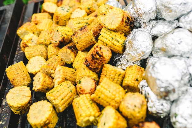 Corn cobs and potatoes wrapped in aluminum foil on a barbecue.