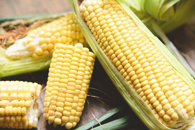 Corn on cobs and sweet corn ears on wood
