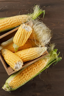 Corn cobs in a wooden box high angle view on a wooden table