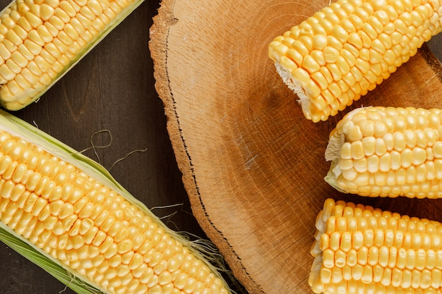 Corn cobs on a wooden piece on a wooden table. flat lay.