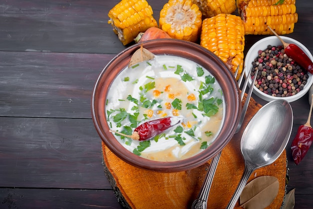 Corn cream soup with sour cream and herbs