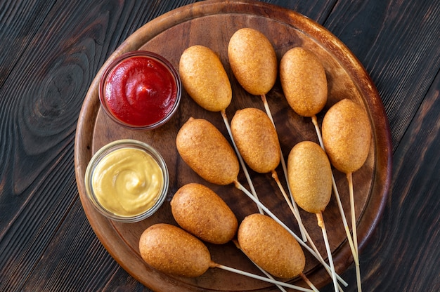Corn dogs with different dip sauces on wooden board