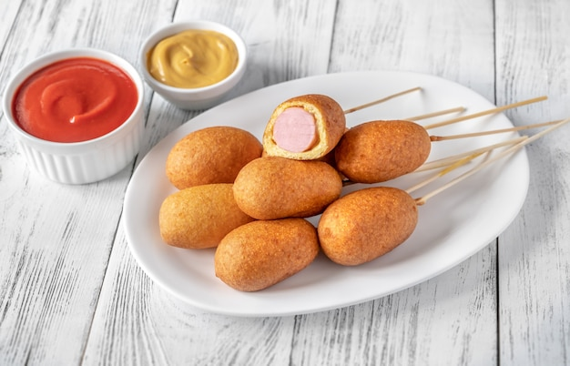 Corn dogs with dip sauces on white serving plate