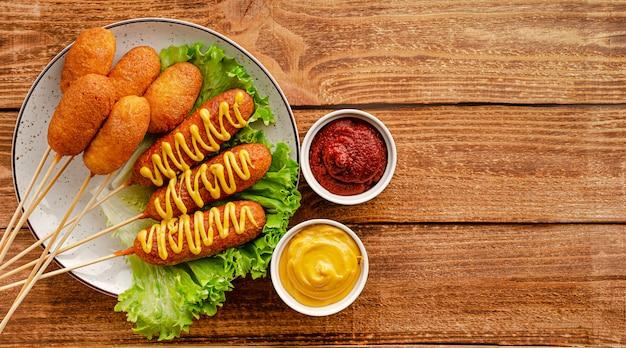 Собаки мозоли с горчицей и кетчуп на деревенском деревянном столе. американская концепция быстрого питания. копировать пространство, накладные расходы.