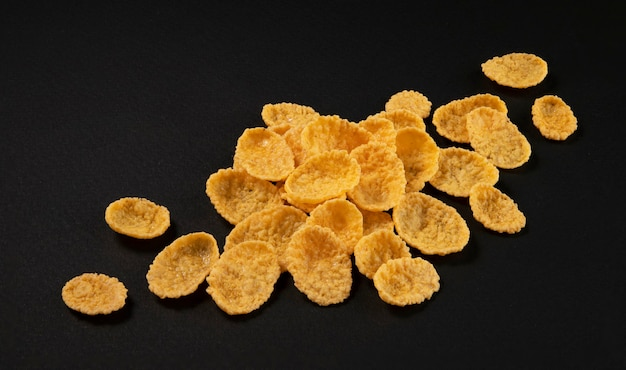 Corn flakes on black background top view
