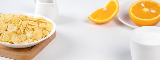 コーンフレークは、白い背景に牛乳とオレンジの甘いものをボウル、クローズアップ、新鮮で健康的な朝食のデザインコンセプトです。