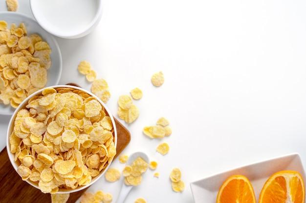 Конфеты шара кукурузных хлопьев с молоком и апельсином на белом фоне, вид сверху, плоский план накладных расходов, свежая и здоровая концепция дизайна завтрака.