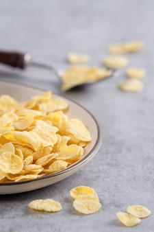 Corn flakes bowl sweeties with milk on gray cement surface, close up, fresh and healthy breakfast design concept.