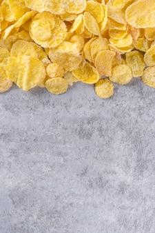 灰色のセメントの背景にコーンフレークボウルのお菓子、上面図フラットレイレイアウトデザイン、新鮮で健康的な朝食のコンセプト。