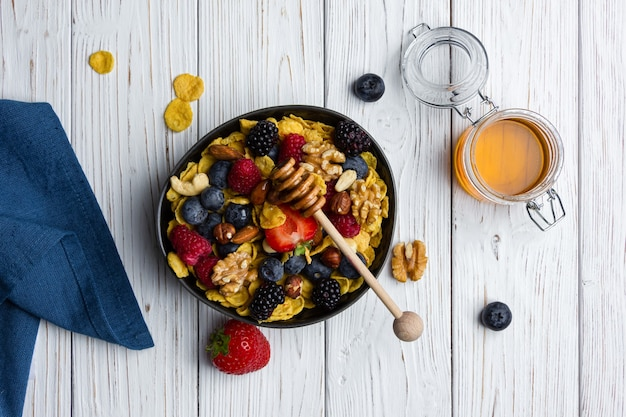 Corn flakes in bowl with berries and nuts on white wooden background. top view of healthy breakfast.