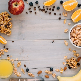 Corn flakes in bowl with fruits and juice