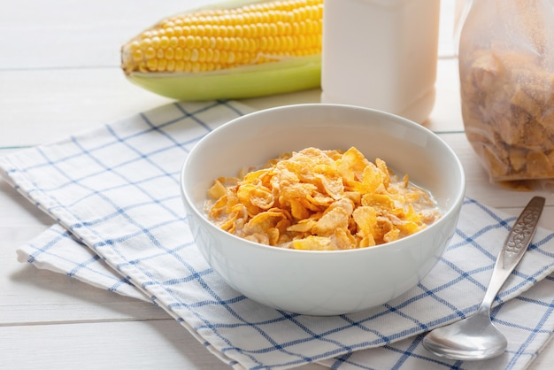 Corn flakes in bowl with milk and cereal corn flakes in plastic pack