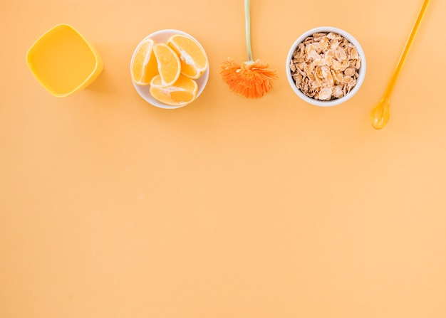 Corn flakes in bowl with orange and juice