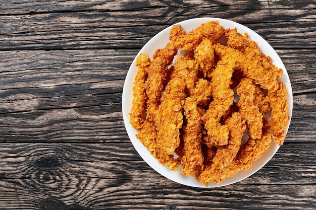 Corn flakes breaded deep fried chicken breast sticks on white plate