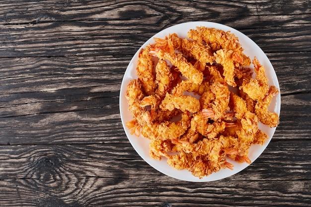 Кукурузные хлопья в панировке с хрустящими креветками во фритюре на белой тарелке на деревянном столе