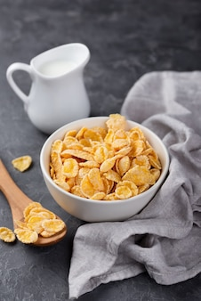 Corn flakes for breakfast in bowl with wooden spoon and milk
