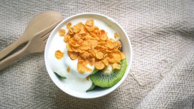 그릇에 콘플레이크, 시리얼, 우유 튀김. 나무 질감 배경의 나무 그릇에 천연 홈메이드 유기농 요구르트