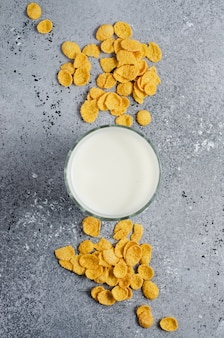 Corn flakes on a concrete background and milk in a glass. flat top view. copy space