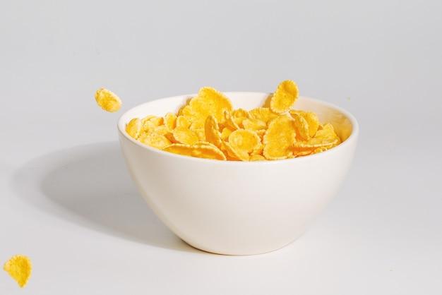 하얀 그릇에 떨어지는 콘플레이크. 운동. 카피스페이스. 화이트에 격리.