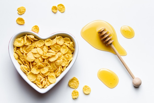 Corn flakes in heart bowl on white background. top view of healthy breakfast.
